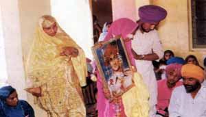 Bibi Surinder Kaur taking laavan with photo of Shaheed Bhai Satwant Singh